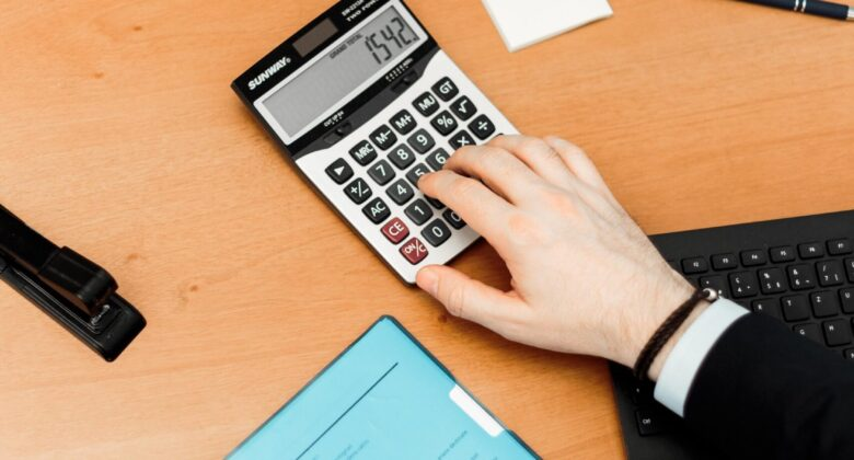 person using calculator on brown wooden surface 2058138 scaled 1